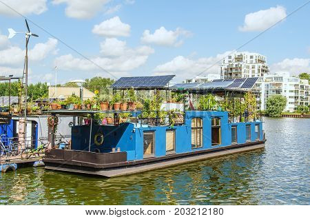 houseboat barge on a river with modern buildings in the background
