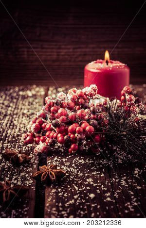 Christmas background with anise cranberries and a red candle. You can use it for a greeting card or voucher.