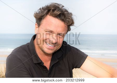 Handsome And Confident. Outdoor Portrait Of Smiling Forties Man On The Beach