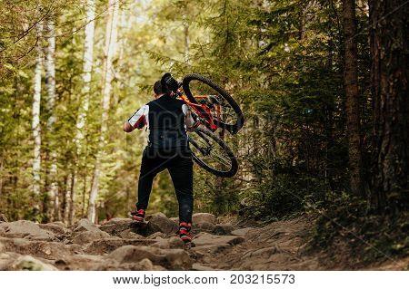 back male cyclist goes stones carry mountain bike