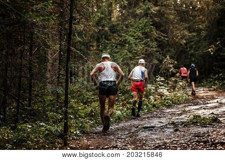 group runners athletes running in forest on muddy and wet trail