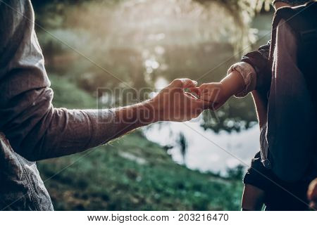 Father And Little Son Holding Hands In Sunlight. Father's Hand Lead His Child Son In Summer Forest N