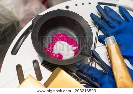 Hairdresser tools for hairdye top view. Hair dye in bowl, gloves for hair coloring