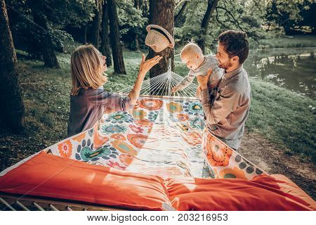Happy Hipster Family Playing With Cute Little Son On Hammock In Summer Sunny Park. Stylish Mom And D