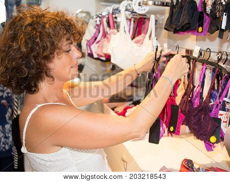 Woman Shopping Lingerie . Shopper Looking And Choosing Clothing Indoors In Store. Beautiful Caucasia