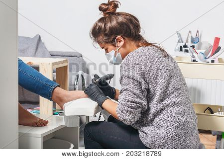 A young white manicurist girl makes a pedicure electric nail drill machine to the client in the workplace. On her face a protective dressing on her hands protective gloves.