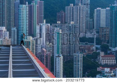 Man on roof shoots skyscrapers and tall residential buildings in Hong Kong, China, view from China Merchants Tower