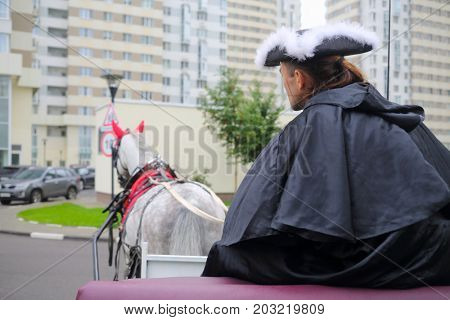 Coachman in black cloak are in couch and horse near residential buildings, back view