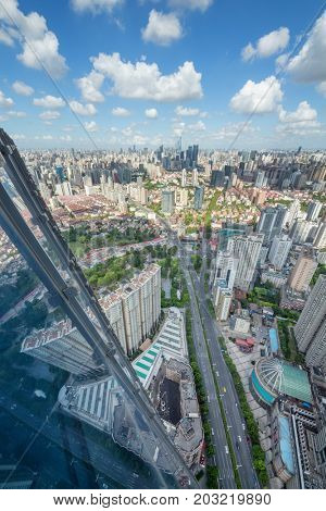 High glass building, road and residential area in big city at sunny day, top view
