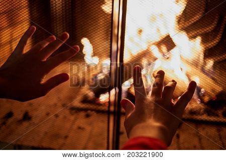 Hands warming at fireplace.