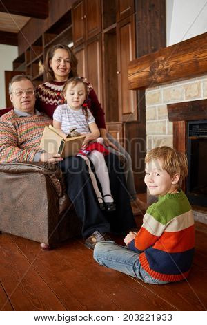 Family of four read book at fireplace.