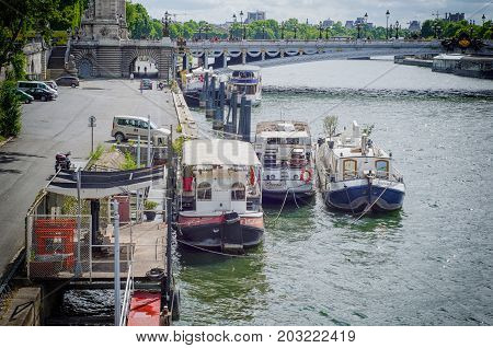 Paris,  France - June 4, 2017: Houseboats are tied along the Port des Champs Elysees on bridge Alexandre III as background