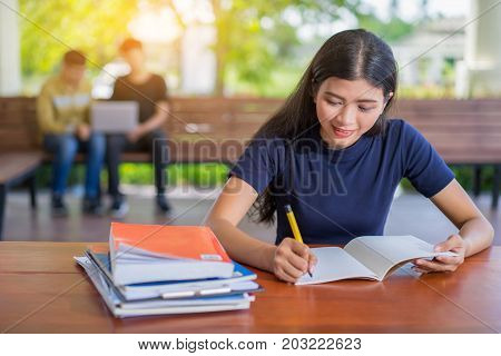 Female student taking notes from a book at library, Young asian woman sitting at table doing assignments in college library