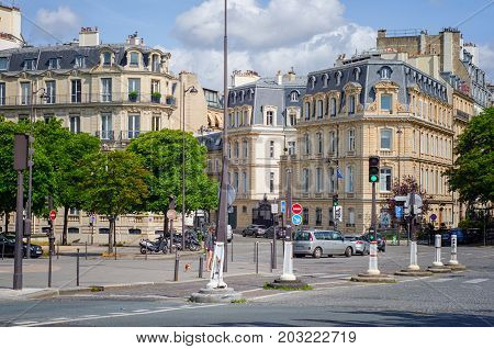 Paris,  France - June 4, 2017: Typical Parisian buildings with attic roofs are located at corner Cours Albert and Rue Francois