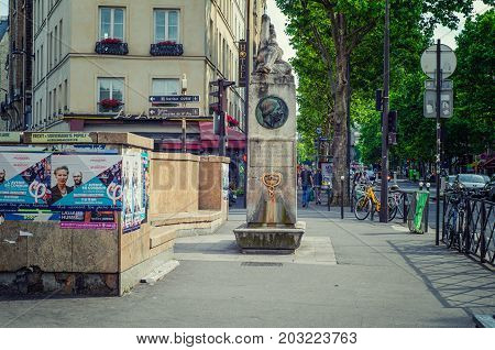Paris, France - June 4, 2017: Monument of Caventou and Pelletier is located at boulevard Saint Michel. In the left side there are campaign posters Legislative elections were in June 2017