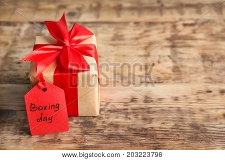 Tag with text BOXING DAY and gift box on table