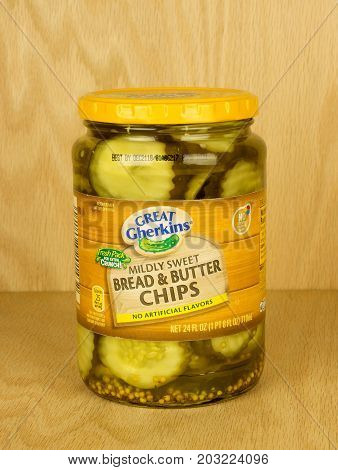 RIVER FALLS,WISCONSIN-SEPTEMBER 07,2017: A jar of Great Gherkins brand bread and butter pickles with a wood background.