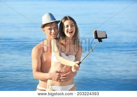 Happy young couple taking selfie on sea beach at resort