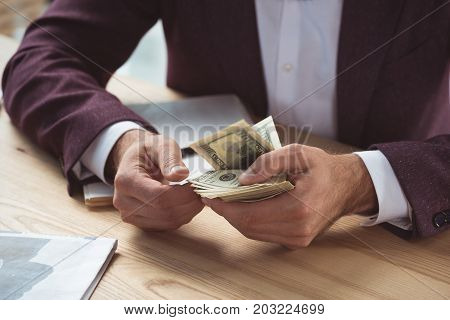 cropped view of businessman counting dollar banknotes salary concept