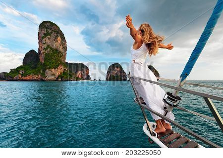 Joyful young woman portrait. Happy girl stand on deck of sailing yacht have fun discovering islands in tropical sea on summer coastal cruise. Travel adventure yachting with kids on family vacation.