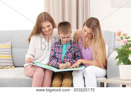 Lesbian couple reading with foster son at home. Adoption concept