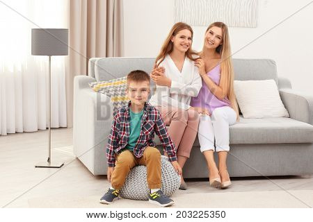 Happy lesbian couple with foster son at home. Adoption concept