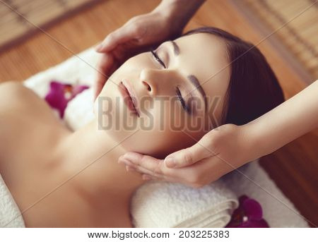 Beautiful girl getting face lifting massage in spa salon. Health care, rejuvenation and relaxation concept.
