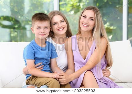 Lesbian mothers with foster son at home. Adoption concept