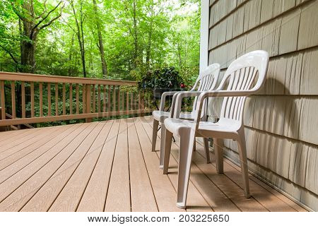 Two chairs on an outdoor deck in the woods. Relaxing and welcoming outdoor scene.