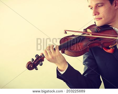 Music passion hobby concept. Young man man dressed elegantly playing on wooden violin. Studio shot on light background