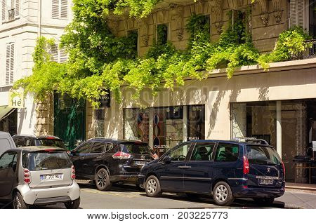 Paris,  France - June 5, 2017: Amazing climbing plants decorate storefront of Bisazza shop which is located in first floor of beige building at 6 Rue de Mezieres