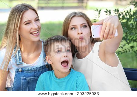 Lesbian mothers with foster son making selfie in park. Adoption concept