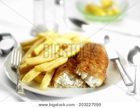 A plate of fish and chips with knife and fork.