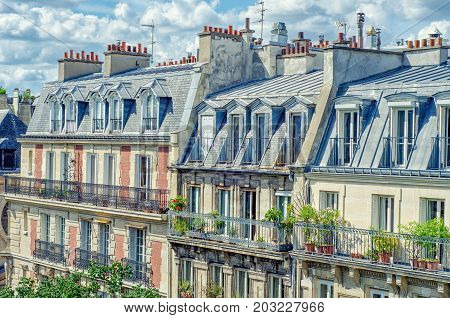 Paris,  France - June 5, 2017: Stunning Parisian attic apartments are located on four story buildings at Rue de l'Abbe de l'Epee. There are green plants growing on balconies of lower floors. Sunny summer day under beautiful clouds