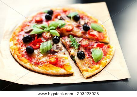 Pizza Margherita with cheese and basil leaf on baking craft paper background with fresh ingredients for you to design and restaurant menu. Delicious Homemade Cheese pizza