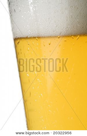 Closeup of condensation on a chilled light beer glass isolated on a white background