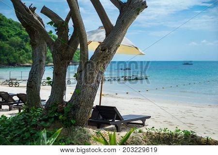 Lonely tropical beach with beach chairs and beach deck