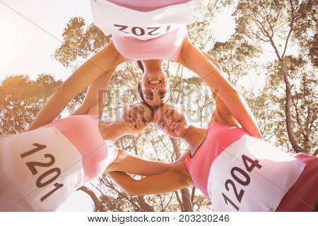 Young athlete women forming huddles in park