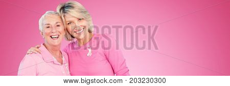 Portrait of happy daughter with mother supporting breast cancer awareness against pink background