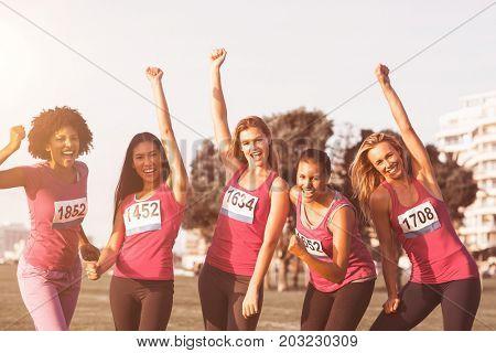 Portrait of cheering women supporting breast cancer marathon in parkland