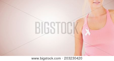 Mid section of woman wearing breast cancer awareness ribbon against neutral background