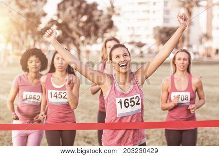 Cheering brunette winning breast cancer marathon in parkland