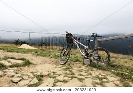 Carpathians. The cyclist left a mountain bike for a respite. The lift is in a thick fog in the background of a mountain landscape.