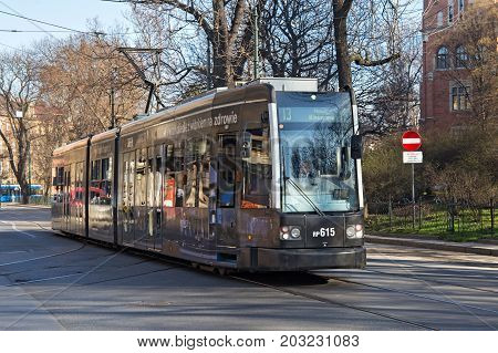 KRAKOW, POLAND - MARCH 28, 2017: Tram Bombardier Flexity Classic in the historic part of Krakow in spring. Total in Krakow more than 90 kilometers of tram tracks and 24 routes.