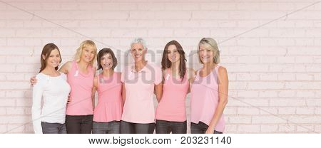 Portrait of smiling women supporting breast cancer social issue against white wall