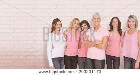 Portrait of confident women supporting breast cancer awareness against white wall