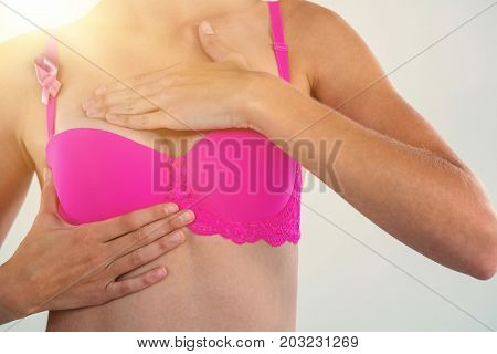 Mid section of sensuous woman in bra with breast cancer awareness ribbon