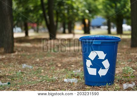 A bright dark blue recycling bin in the park or wood. A colorful plastic container for rubbish recycling on a blurred natural background. Environment, ecology, nature protection, pollution concept.