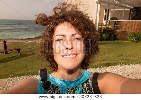 Forties Woman Smiling On The Beach Making A Selfie At Sunset