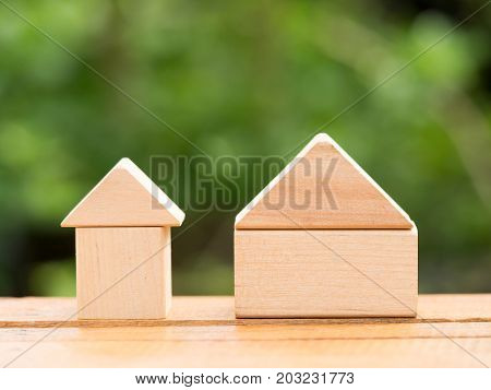 Big wooden home and small wooden home on floor with green background. Home loan or building home concept.